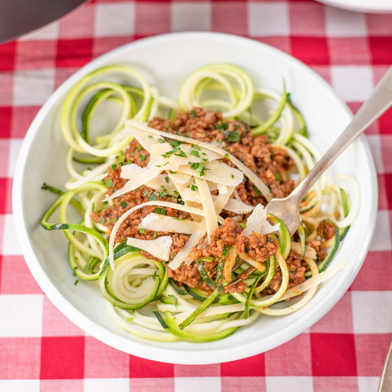 Keto Bolognese Sauce in a bowl with zucchini noodles and parmesan cheese on a red checked table