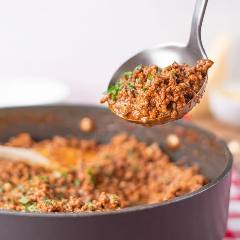 Keto Bolognese Sauce being ladled out of a saucepan