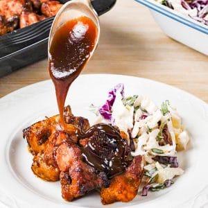 Pouring Keto BBQ Sauce over Pork