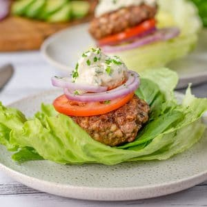 Keto Lamb & Halloumi Burgers in a lettuce wrap topped with tomato and onion