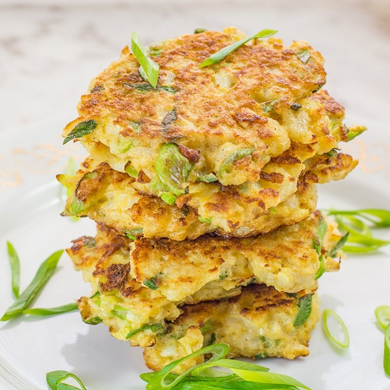 Low Carb Cauliflower Latkes stacked on a plate and topped with scallins