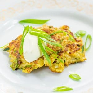 Keto Cauliflower Latkes on a plate topped with scallions and sour cream