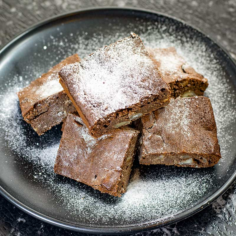 Keto Chocolate Macadamia Brownies on a plate covered with icing sweetener