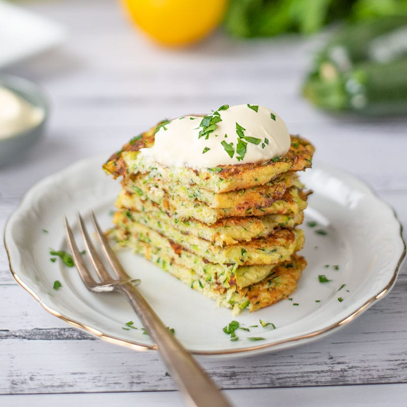 Keto Zucchini Fritters on a plate with a slice cut off the left side