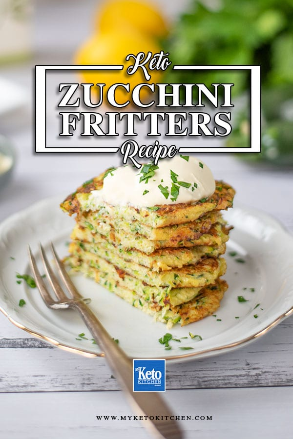 Keto Zucchini Fritters stacked on a plate and topped with sour cream and chopped parsley.