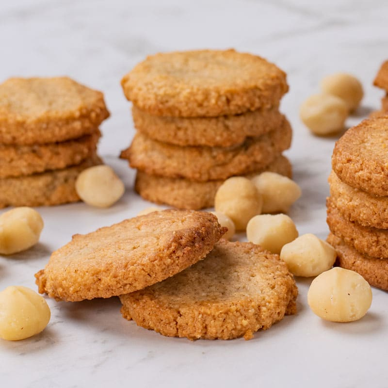 Keto Macadamia Cookies stacked in a pile on a marble table