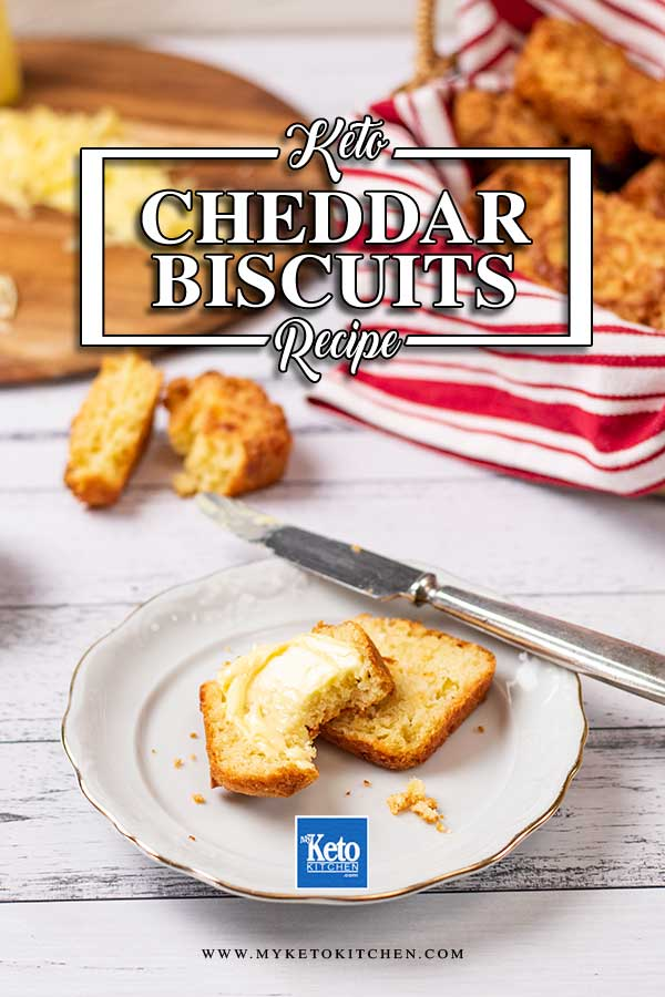 Low Carb Cheddar Biscuits cut in half and buttered on a plate