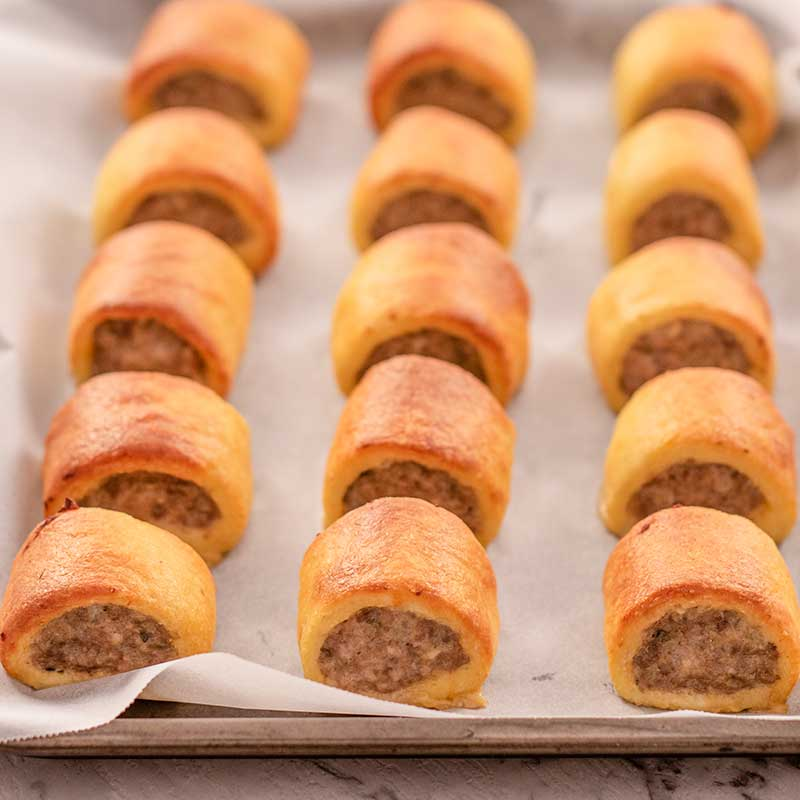 Image of cooked keto sausage rolls on a baking tray lined with parchment paper