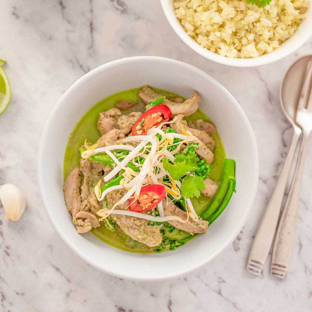 Image shows keto thai chicken green curry in a white bowl topped with bean sprouts, cilantro and a slice of red pepper. There are utensil and a bowl of cauliflower rice in the background