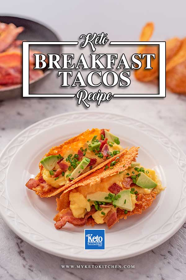 Imago shows two keto breakfast tacos on a white plate. The tacos are filled with bacon, scrambled eggs, avocado and chives.