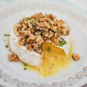 Image of a wheel of brie cheese on a white plate topped with walnuts, thyme and sugar free maple syrup with one slice remove. The melted cheese is oozing out.