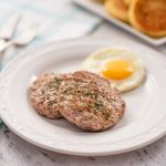 Image shows two keto breakfast sausage patties with a fried egg on a white plate