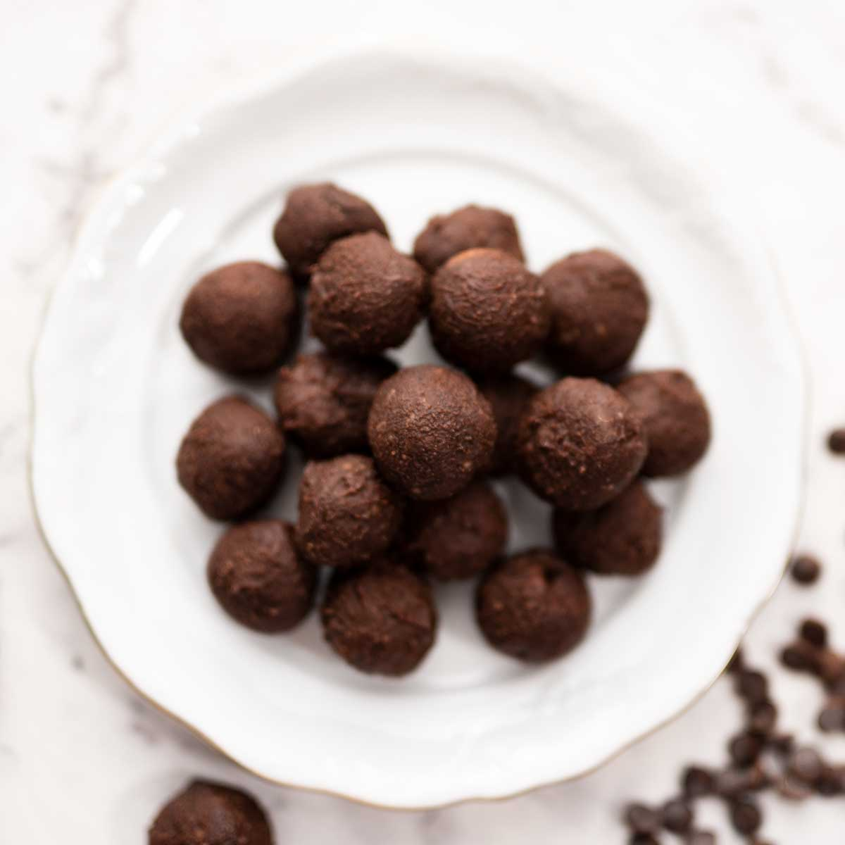 Image shows a white plate piled wiith keto brownie fat bomb balls
