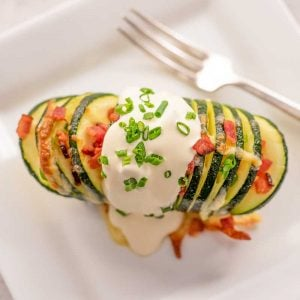Image of a keto hasselback zucchini stuffed with cheese and bacon with sour cream and chives on top, sitting on a white plate with a silver fork