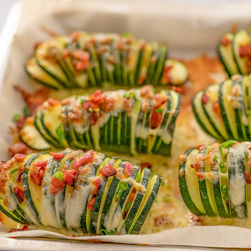 Image of 6 pieces of keto hasselback zucchini stuffed with cheese and bacon sitting on a cookie sheet