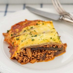 Image of Keto Moussaka on a white plate with a silver knife and fork in the background