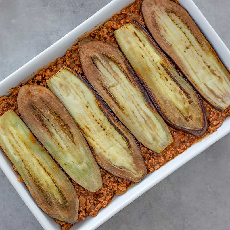 Image of a rectangle casserole dish layered with ground lamb sauce and grilled eggplant, sitting on a grey background