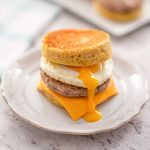 Image of a keto sausage and egg muffin with egg yolk dripping down the front, it is sitting on a white plate