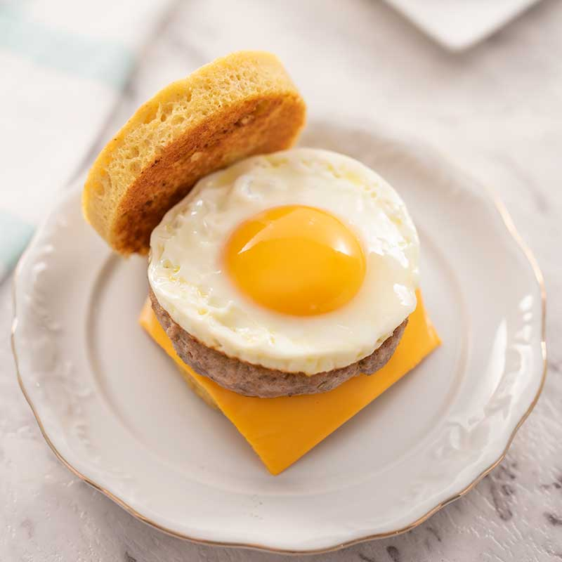 Image shows a keto sausage and egg muffin with the top bread on the side, sitting on a white plate