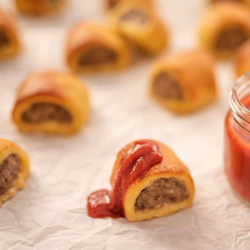 Image of bite sized keto sausage rolls one is drizzled with tomato ketchup