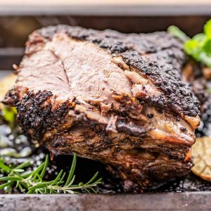 Image show a cooked lamb shoulder in a roasting pan with fresh rosemary, and mint