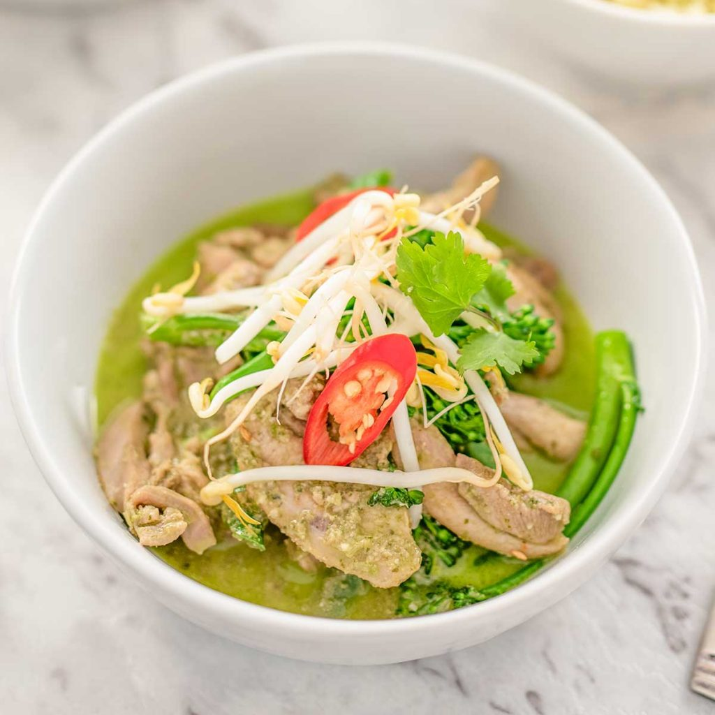 Image shows keto thai chicken green curry in a white bowl topped with bean sprouts, cilantro and a slice of red pepper