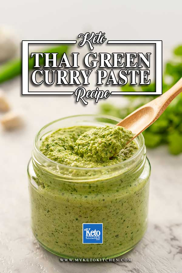 Image shows a wooden scoop filled with low carb thai green curry paste, the jar of curry paste is in the background
