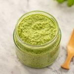 Image of keto thai green curry paste in a glass jar with a white background
