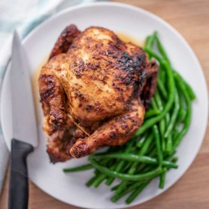 Image of a rotisserie chicken on a white plate with green beans around it on one side and a carving knife on the other.
