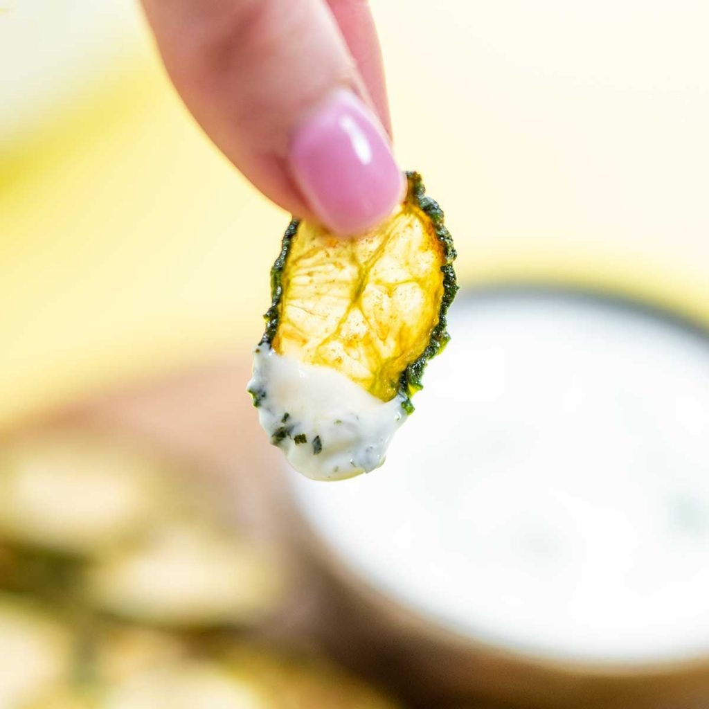 A Keto Cucumber Chip with creamy dip on the end being held to the camera