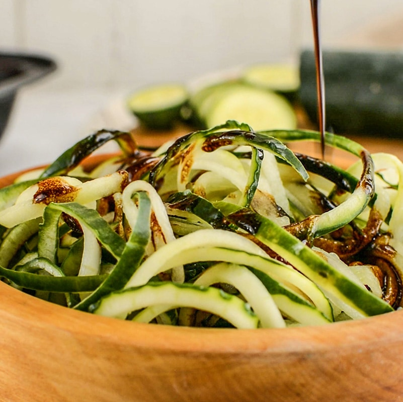 Keto Cucumber Noodle Salad with dressing poured over