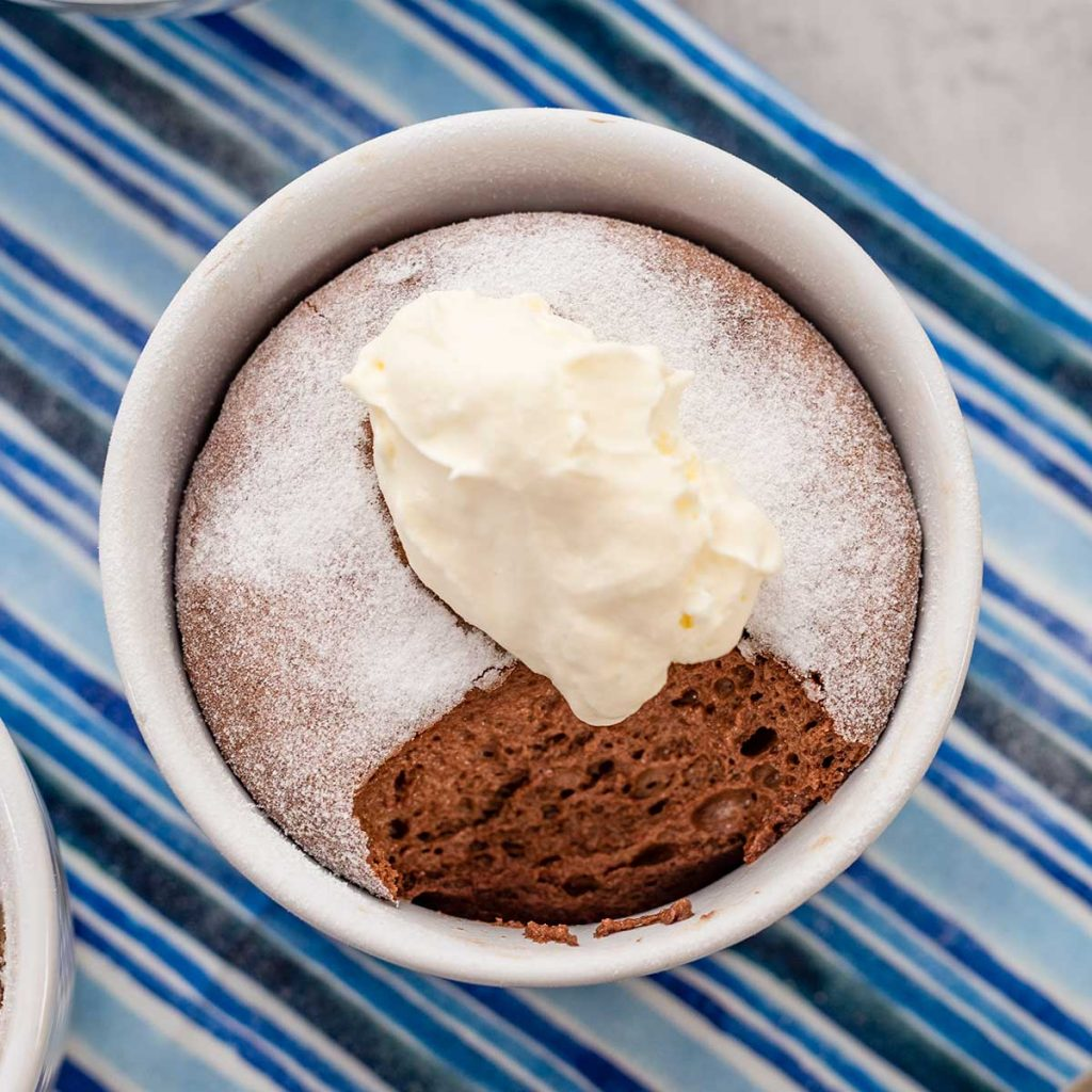 Keto Chocolate Souffle topped with whipped cream on a striped blue napkin