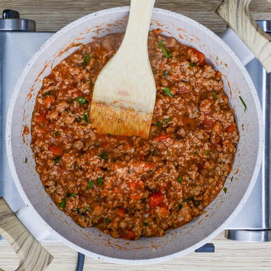 Keto Sausage pasta ingredients simmering in a white saucepan