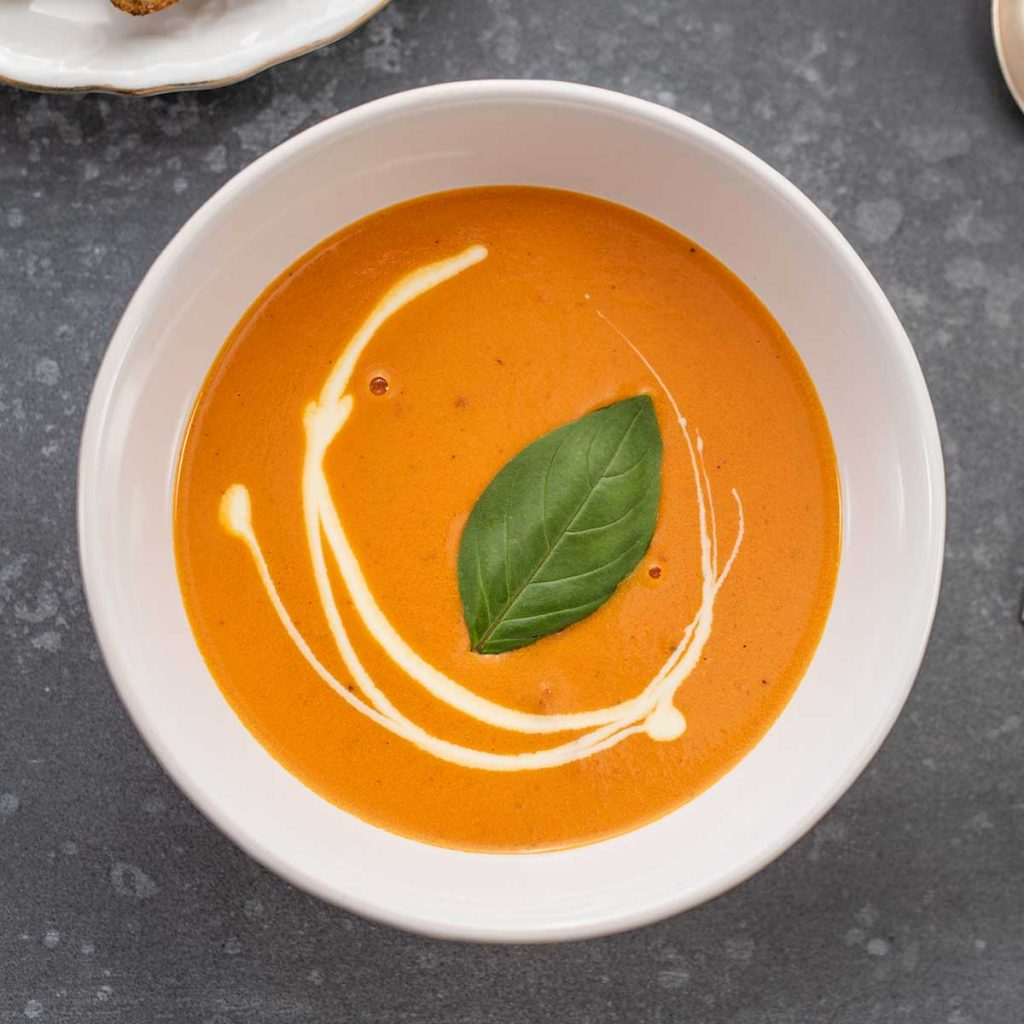 Keto Creamy Tomato Soup in a white bowl on a dark grey table