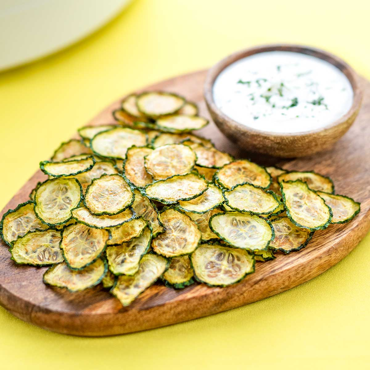 Keto Cucumber Chips on a wooden board with a bowl of creamy dip on a yellow background