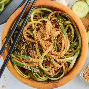 Keto Cucumber Salad in a wooden bowl with chopsticks resting on the side