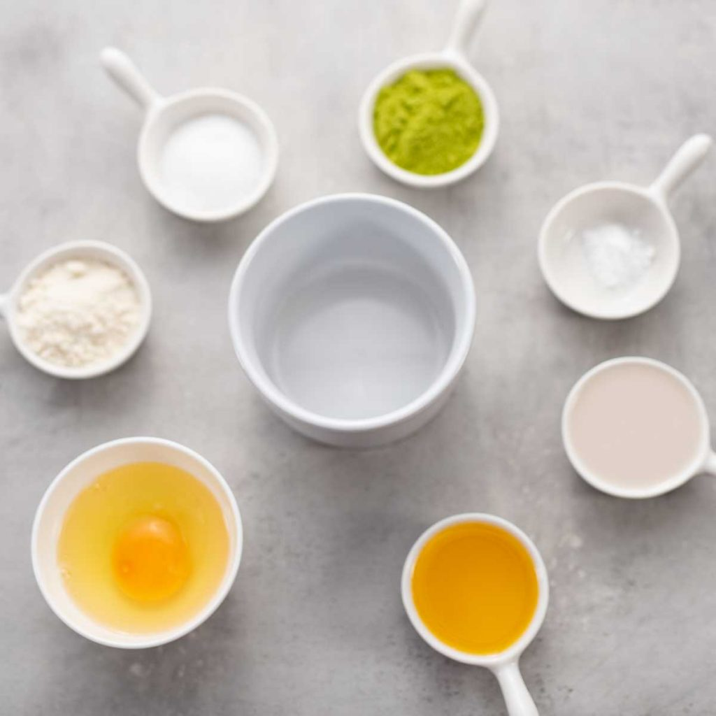 Ingredients for a keto matcha mug cake surrounding a white ramekin