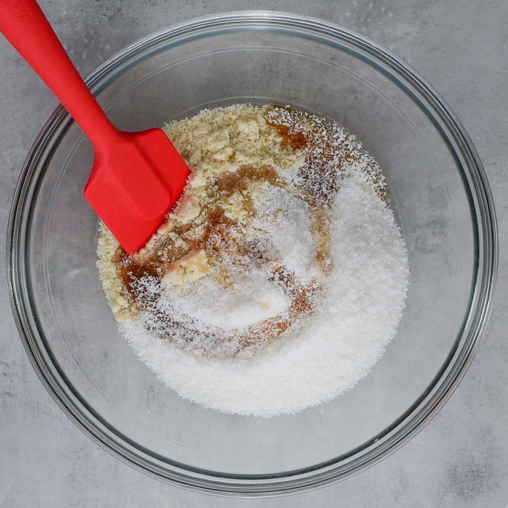 Keto Snowball Cookies ingredients in a mixing bowl with a red spatula