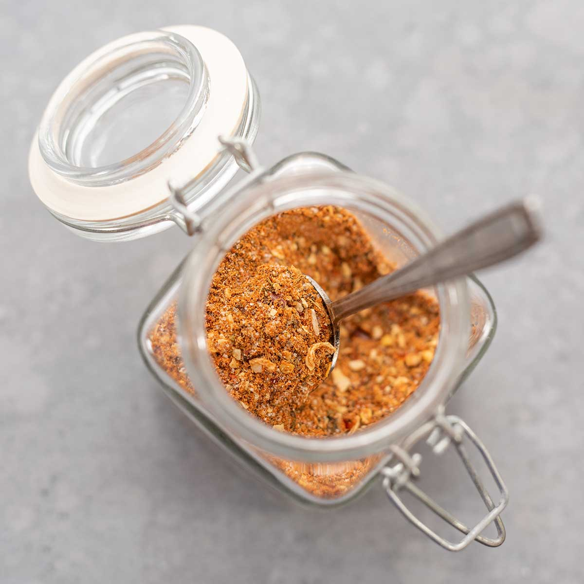 Montreal steak seasoning in a glass jar with a spoon sticking out