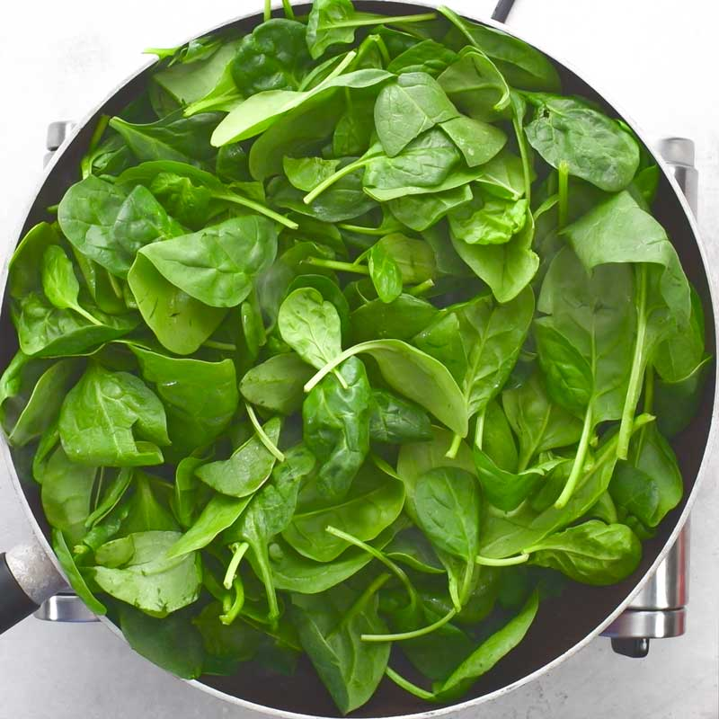 Spinach sauteing in a pan for to make Keto Creamed Spinach