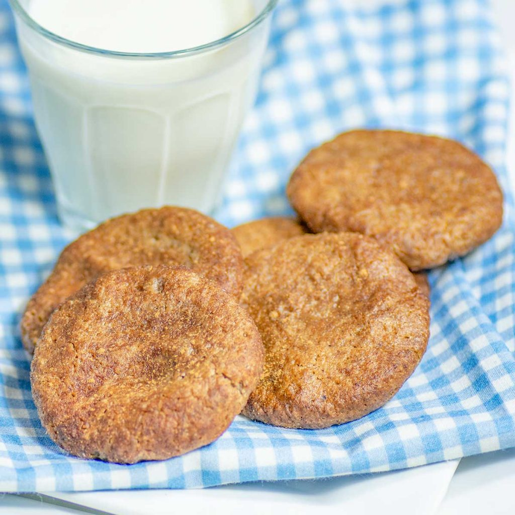 Keto Cinnamon Walnut Butter Cookies on a blue checked napkin with a glass of milk