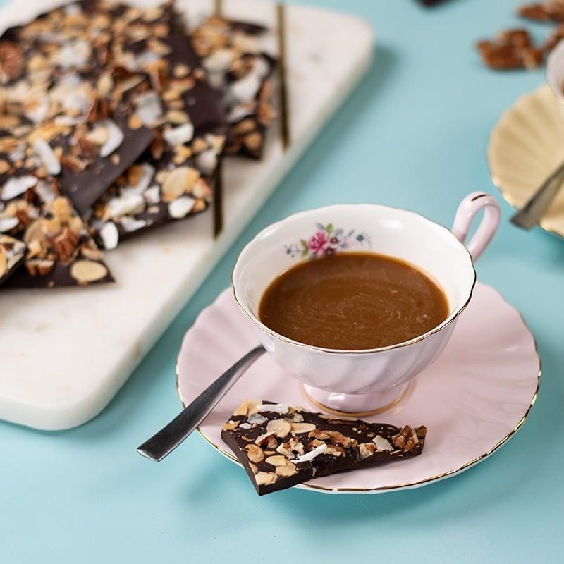 Keto Chocolate Sea Salt Bark on the saucer of a cup of coffee