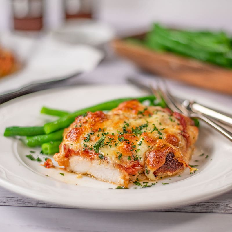Keto Chicken Parmigiana on a plate with green beans