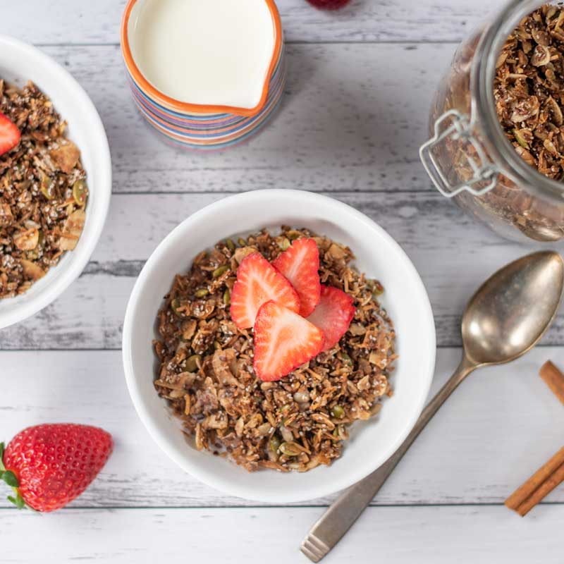 Keto Cinnamon Granola Cereal in a bowl topped with strawberries