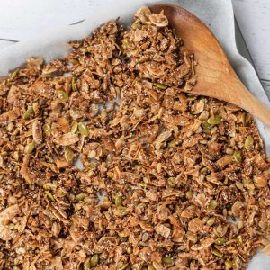 Keto Cinnamon Cereal on a baking sheet with a wooden spoon