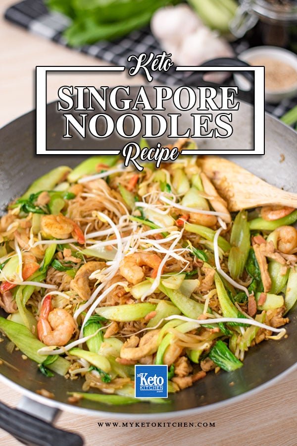 Keto Singapore Noodles in a wok with a wooden utensil tucked under the noodles on the right.