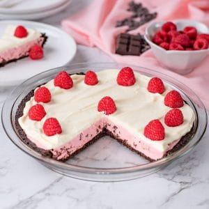 Keto Raspberry Cream Pie in a glass pie dish with a slice missing