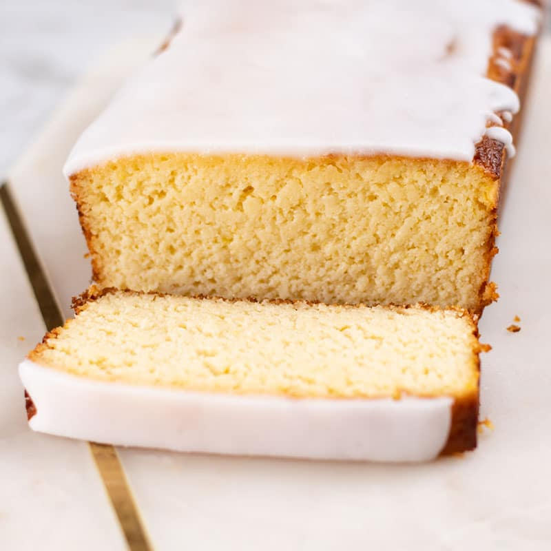 Keto Yogurt Cake on a marble slab with a slice cut to reveal the moist texture of the cake.