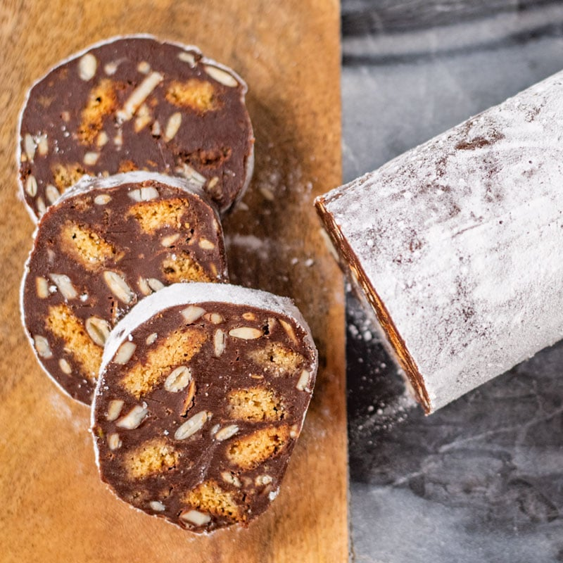 Keto Chocolate Salami sliced on a wooden and marble board