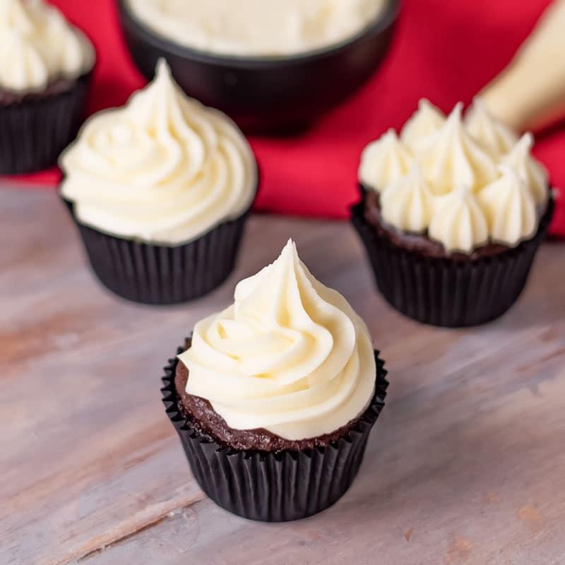 Keto Vanilla Buttercream piped onto chocolate cupcakes